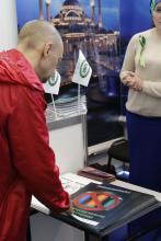 Посетители выставки разбирают брошюры